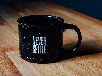 A coffee mug sitting on a table that says 'Never Settle', showing our commitment to Website Security